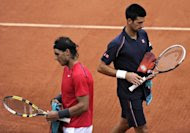 Spain's Rafael Nadal (L) passes by Serbia's Novak Djokovic during their Men's Singles final tennis match of the French Open tennis tournament at the Roland Garros stadium in Paris. Nadal and Djokovic were locked in a tight French Open final duel Sunday when rain caused a suspension until Monday, only the second time in history that the tournament has not finished on time. (AFP Photo/Pascal Guyot)