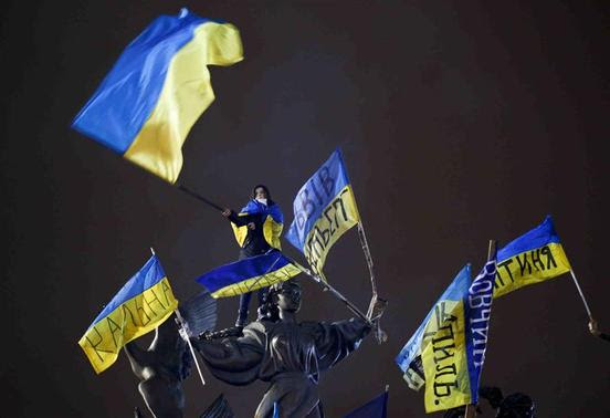 A Pro-European integration protester waves a Ukrainian national flag as she stands on a statue during a mass rally at Independence Square in Kiev in this December 15, 2013 file photo. REUTERS-Marko Djurica-Files