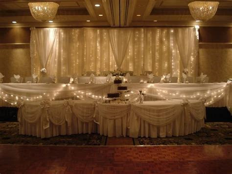 Tiered wedding head table w/ lighted backdrop, serpentine