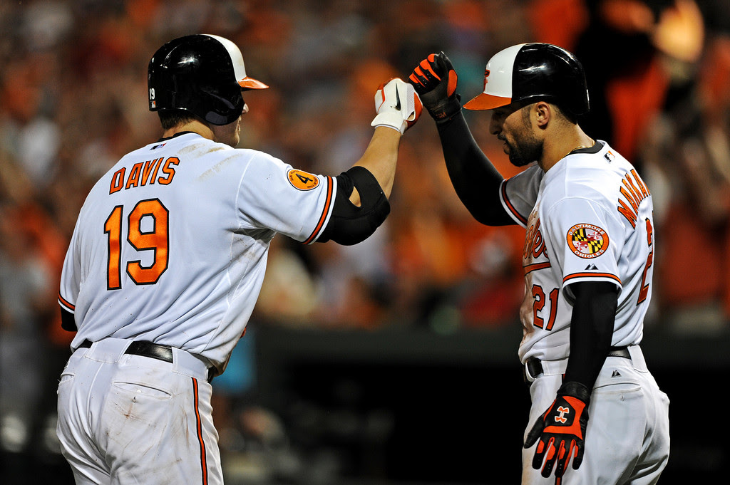 Designated hitter Chris Davis #19 of the Baltimore Orioles high-fives teammate Nick Markakis #21after hitting a two-run home run in the seventh inning against the Washington Nationals during an interleague game at Oriole Park at Camden Yards on May 29, 2013 in Baltimore, Maryland. The Baltimore Orioles won, 9-6.