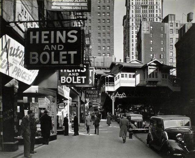 Radio Row, Cortlandt Street, Manhattan. Men window shop in store selling radios, elevated railroad station, Ninth Avenue line, right center, subway entrance visible.