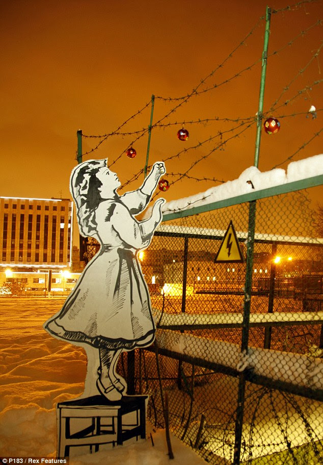 Seasonal: A cut-out of a ghostly girl hanging baubles on barbed wire popped up in central Moscow last month