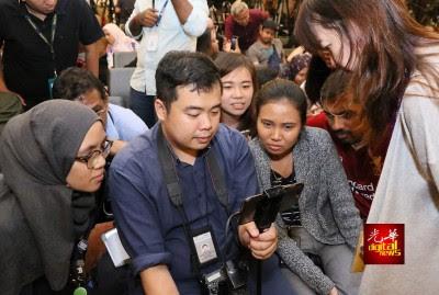 媒体等候马哈迪以新任首相身份召开的首个新闻发布会时,迫不及待围在一块观看宣誓转播。