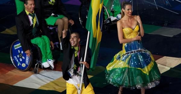 Cadeirantes carregam bandeira do Comitê Paraolímpico durante cerimônia de abertura dos Jogos