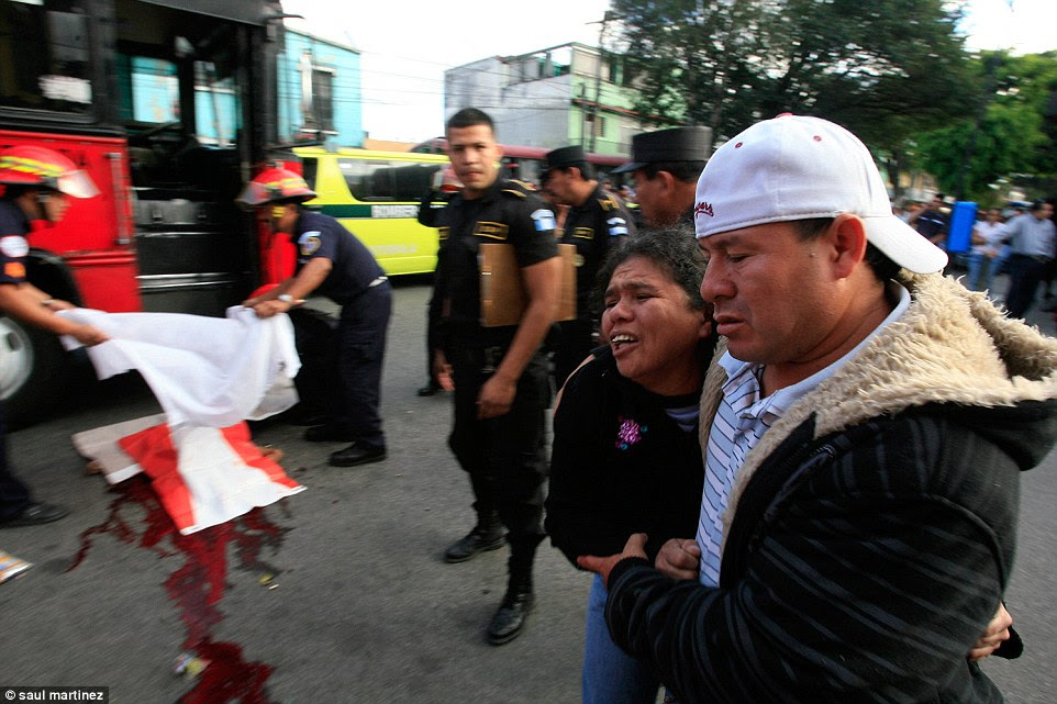 Grief: A mother and father hold each other after seeing the body of their son, a bus driver, who is believed to have been killed by gang members because he did not pay extortion