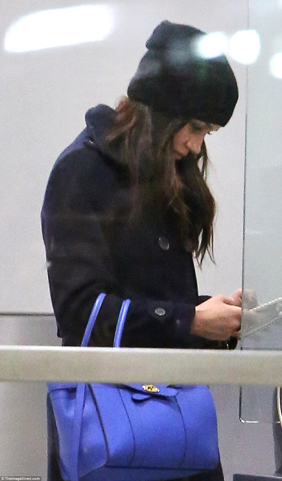 Missing Harry already? The prince's girlfriend was glued to her phone as she touched down in Toronto