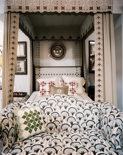 Bedroom - A patterned settee at the foot of a canopy bed