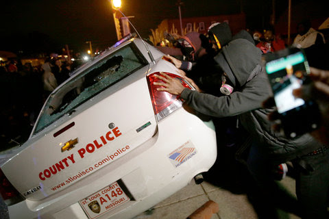 Protesters in Ferguson trying to turn over a St. Louis County police vehicle
