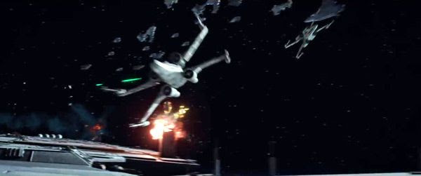 Two X-Wing starfighters attack a large structure in space while the Rebel Fleet looms in the background...in ROGUE ONE: A STAR WARS STORY.