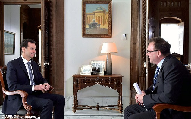 Syrian President Bashar al-Assad (left) is pictured answering questions during an interview with German public broadcaster ARD in the Syrian capital Damascus yesterday. He offered 'full amnesty' to Syrian rebels