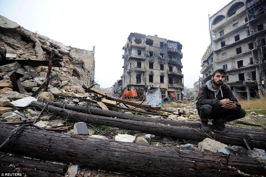 Um homem senta-se em meio a detritos perto Umayyad mesquita, na área controlada pelo governo de Aleppo, durante uma visita da imprensa, Síria
