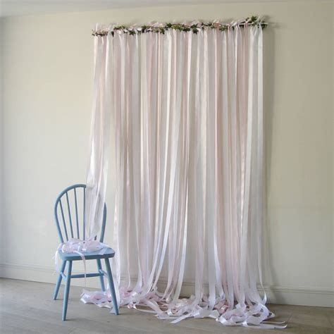 pale pink ribbon backdrop on white pole with ivy by just