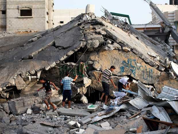 Palestinos inspecionam escombros de uma mesquita destruída após um ataque militar israelense no campo de refugiados de Nusseirat, no centro da Faixa de Gaza. (Foto: Thomas Coex / AFP Photo)