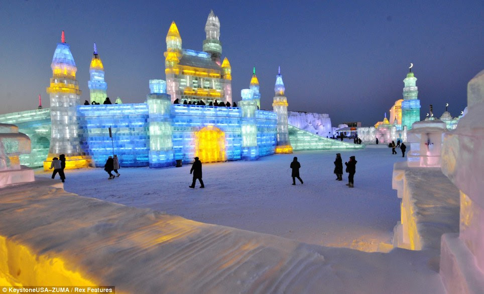 Whiter shade of pale: Tourists flock on and around the ice palaces as darkness falls in preparations for the opening ceremony