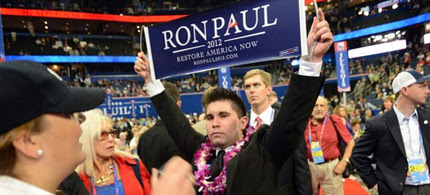 A security agent calls for more security as delegate from Virginia Braedon Wilkerson displays a Ron Paul sign after the vote on Maine at the Tampa Bay Times Forum in Tampa, Florida, during the Republican National Convention, 08/28/12. (photo: Getty Images)