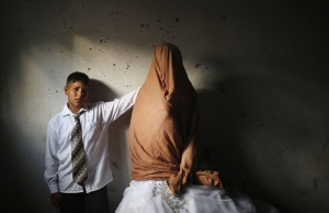 Young Palestinian groom Ahmed Soboh, 15 and his bride Tala, 14, stand inside Tala's house which was damaged during an Israeli strike in 2009, during their wedding party in the town of Beit Lahiya, near the border between Israeli and northern Gaza Strip September 24, 2013. REUTERS/Mohammed Salem