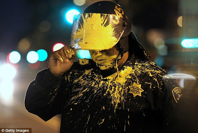Target: An Oakland police officer is hit in the face with paint after advancing on activists blocking an intersection