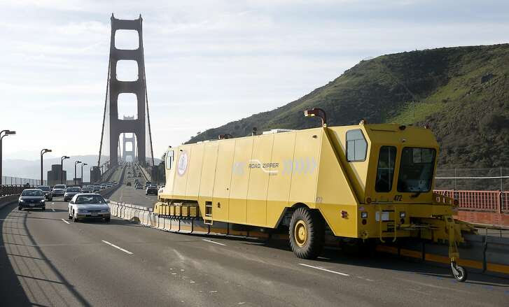 Northbound traffic (left) rolls past a zipper truck reconfiguring lanes on the Golden Gate Bridge to three in each direction after the morning rush in Sausalito, Calif. on Tuesday, Jan. 12, 2016. One year has passed since a movable median barrier was installed on the bridge.