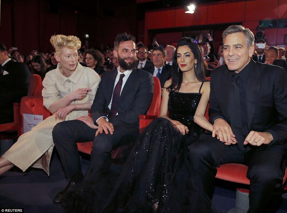 Not your average double date: Amal sat pretty alongside George, his co-star Tilda Swinton and her partnerSandro Kopp inside the venue