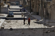 RETRANSMISSION FOR ALTERNATIVE CROP -- Two Syrian boys play on a street next to a building hit by a Syrian government airstrike in Aleppo, Syria, Sunday, Aug. 19, 2012. (AP Photo/ Khalil Hamra)