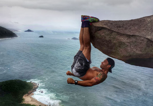 MAN HANGING OFF ROCK