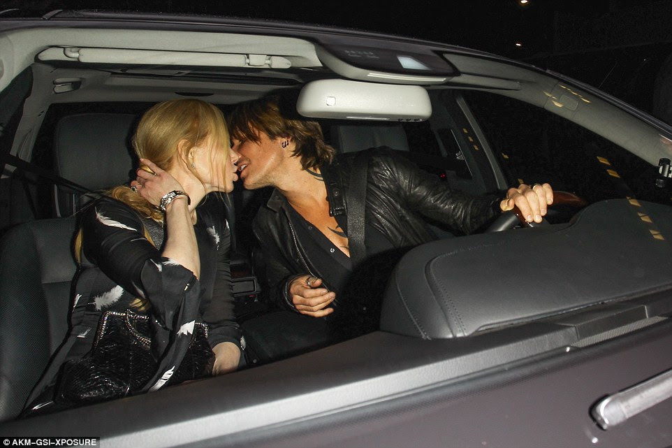 Goodnight kiss: Keith took command of the wheel while his wife leaned in for a smooch after their night out