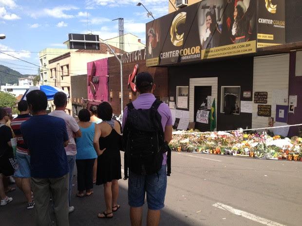 Pessoas observam a fachada do prédio onde funcionava a boate Kiss (Foto: Iara Lemos/G1)