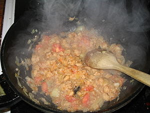 Frying chopped onions and tomatoes in a frying pan