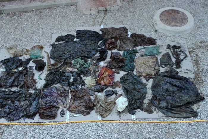 An assortment of plastic rubbish, including bags and wrappers, laid out on the ground.