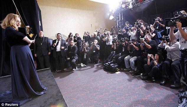Saudação à imprensa: Após a cerimônia, Adele posou para os fotógrafos nos bastidores com seus gongos