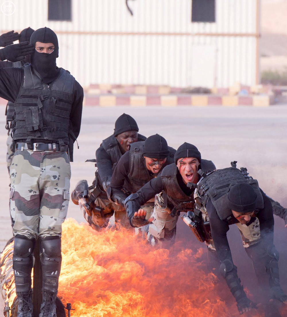 Members of Saudi security forces cross through a fire during a military exercise west of Riyadh, Saudi Arabia