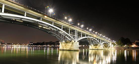 Das Bild zeigt eine hell erleuchtete Brücke.