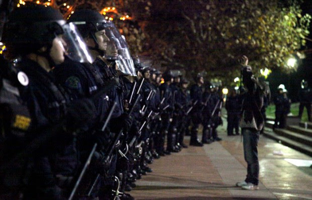 A protester raises his arms in front of a line of police wearing riot gear on Sproul Plaza.