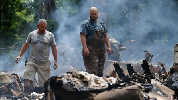 Men look at the remnants of a house which was torn off its foundation and burned after severe flooding in West Virginia on 24 June