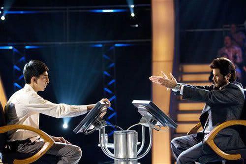 Jamal Malik (Dev Patel) takes on game show host Prem Kumar (Anil Kapoor) in SLUMDOG MILLIONAIRE.