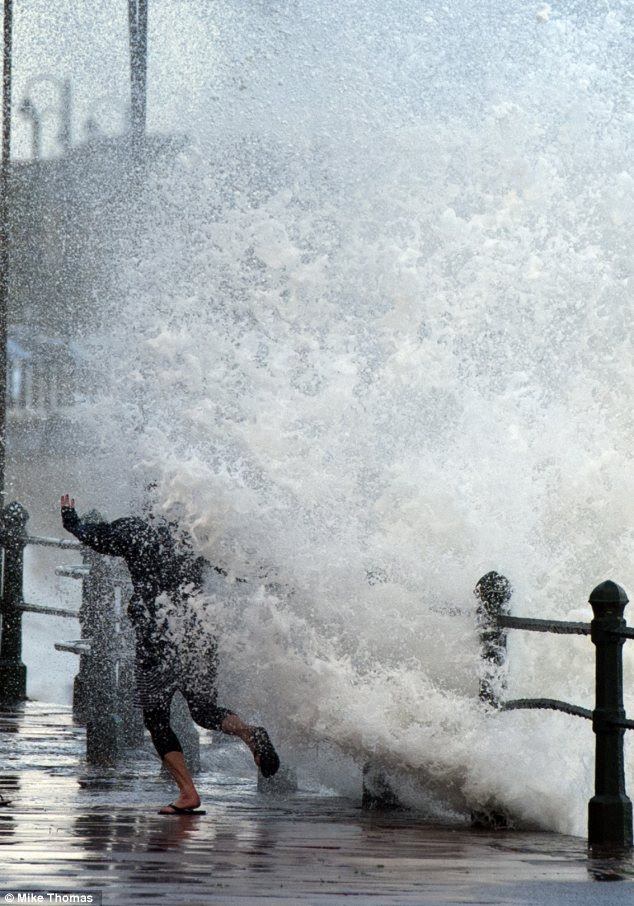 A mother and son play with the waves on Penzance sea front, dispite the road being closed for safety reasons