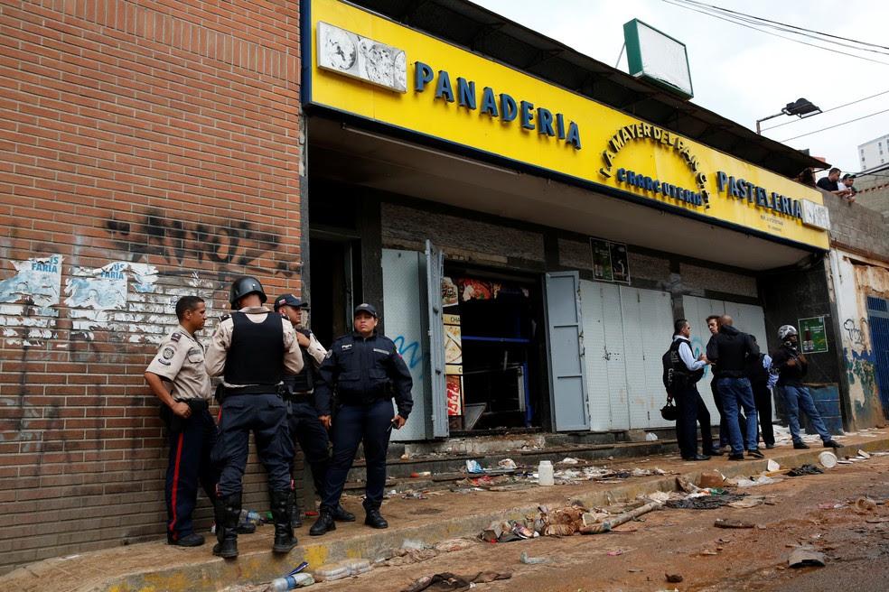 Policiais e investigadores em frente à padaria saqueada em Caracas (Foto: Reuters)