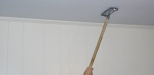 Sanding the ceiling with a long handled, drywall sanding pad