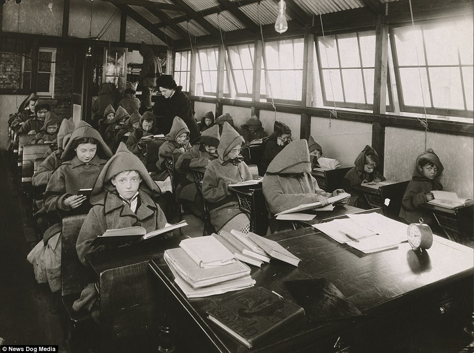 Children shiver as they sit at desks, wearing hooded coats in an open-air school in Chicago, Illinois, circa 1900s