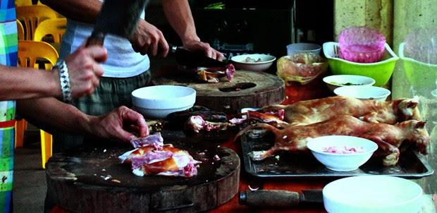 Cozinheiros preparam a carne de gato em um retaurante em Hanói (Foto: AFP Photo)