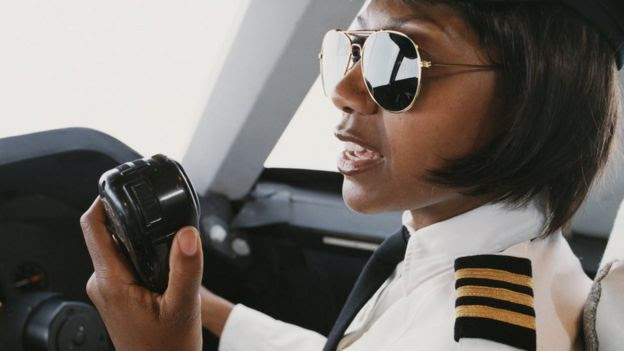 Una mujer piloto comunicándose a través de la radio desde el avión.