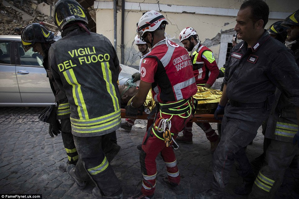 A survivor of the earthquake is transported on a stretched after being pulled out from rubble on Thursday