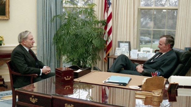 Former President George HW Bush (R) and David Rockefeller speak in the Oval Office at the White House in this undated photo.