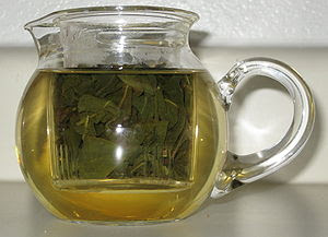A small tea pot filled with loose leaf Oolong