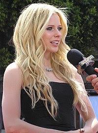 Lavigne em Los Angeles, na premiação de Over the Hedge, no qual dublou a personagem Heather. A cantora está sendo entrevistada com um microfone. Seu corpo está em posição lateral e possui a boca ligeiramente aberta. Avril está de roupa preta, seu braço e colo descobertos. Usa um colar.