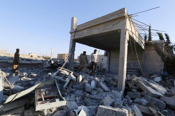 Men inspect a damaged plastics factory that was targeted on Sunday by what activists said were U.S.-led air strikes at the Islamic State's stronghold of Raqqa, September 29, 2014. REUTERS/Stringer