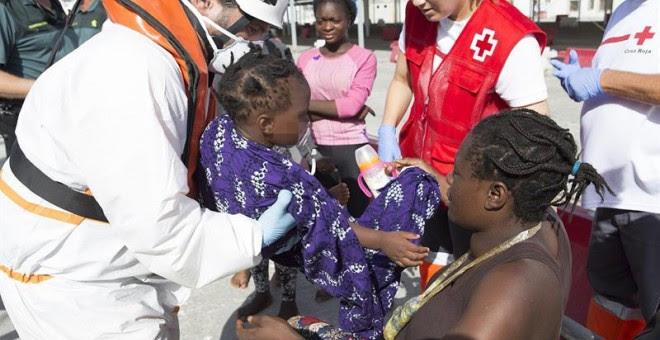 Una mujer con su bebé es ayudada a bajar en el puerto de Motril (Granada) donde han sido trasladados después de que Salvamento Marítimo haya rescatado hoy a un total de 34 personas cuando viajaban en una patera a 7,5 millas al sur de la isla de Alborán. E