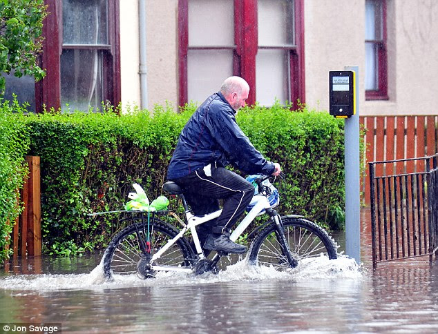Heavy rain also caused flooding in DUNBAR, East Lothian. Here a cyclist struggles to make his way down the road following flooding