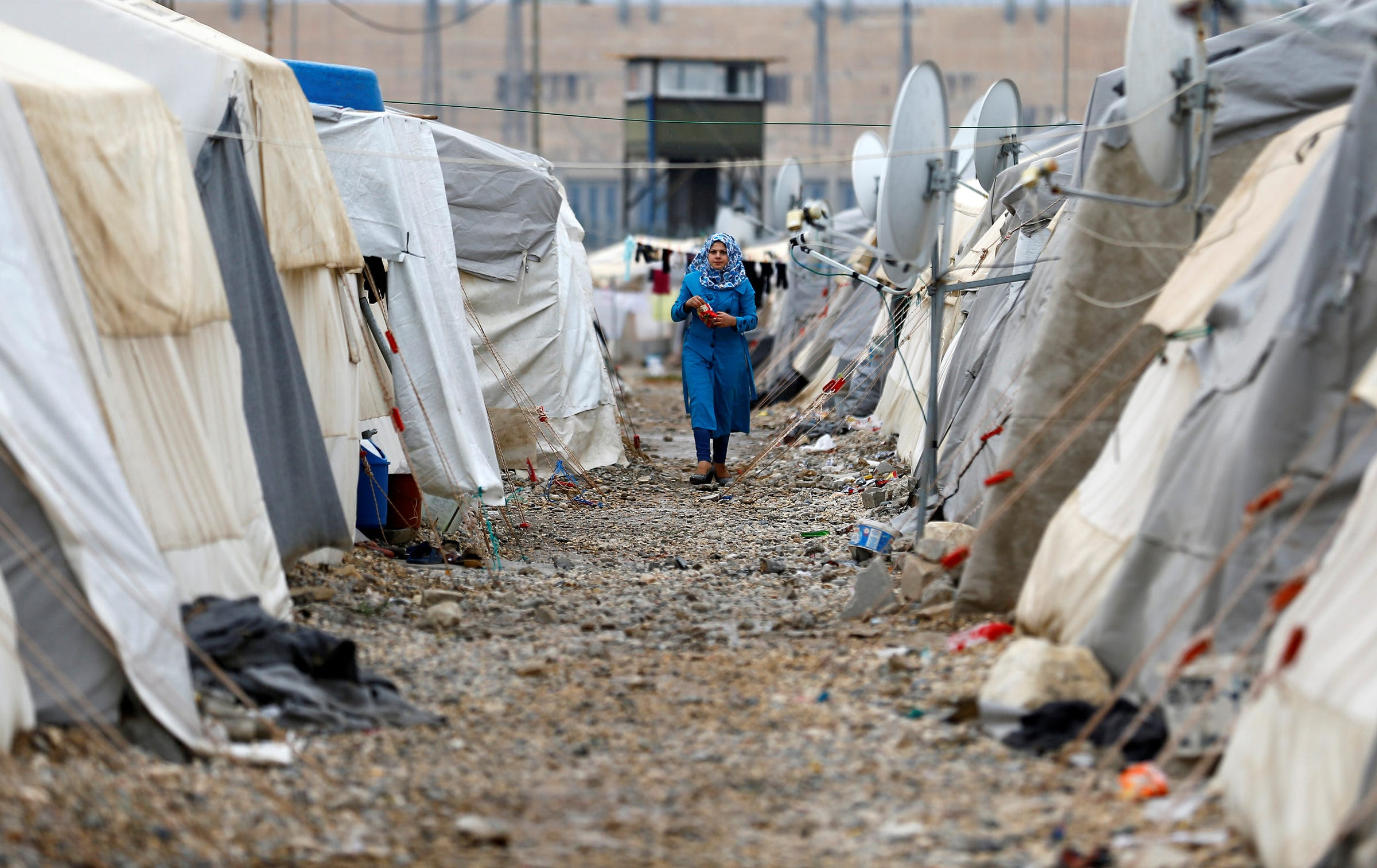 A Syrian refugee woman walks between tents in Nizip refugee camp, near the Turkish-Syrian border in Gaziantep province, Turkey, November 30, 2016.