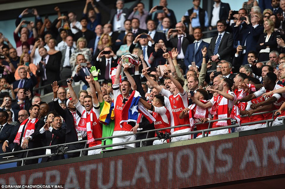 German centre half Per Mertesacker raises the FA Cup above his head as Arsenal's triumphant players celebrate